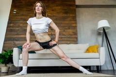 Mujer rubia joven que hace estirando ejercicios de la yoga en casa Forma de vida sana imagenes de archivo