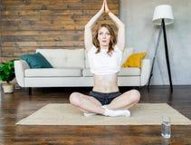 Mujer rubia joven que hace estirando ejercicios de la yoga en casa Forma de vida sana fotos de archivo