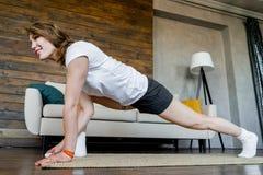 Mujer rubia joven que hace estirando ejercicios de la yoga en casa Forma de vida sana foto de archivo