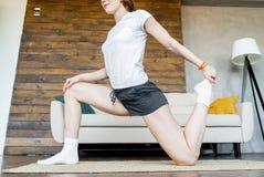 Mujer rubia joven que hace estirando ejercicios de la yoga en casa Forma de vida sana imagen de archivo
