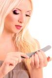 Mujer rubia joven que hace sus uñas Fotografía de archivo libre de regalías