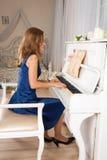 Mujer rubia joven que juega el piano imagen de archivo libre de regalías