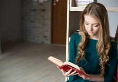Mujer rubia joven que lee un libro Imágenes de archivo libres de regalías