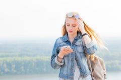 Mujer rubia joven que lee un mensaje que vino al smartphone en naturaleza Internet, tecnología imagen de archivo