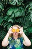 Mujer rubia joven que lleva a cabo las rebanadas de mandarina anaranjada delante de sus ojos, besándose imagen de archivo libre de regalías