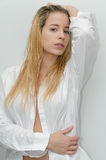 Mujer rubia joven que lleva una camisa blanca Foto de archivo