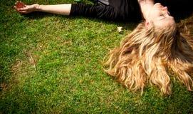 Mujer rubia joven que miente en la hierba. Fotografía de archivo