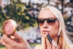 Mujer rubia joven que mira en un peque?o espejo en la calle y el corret su barra de labios fotografía de archivo