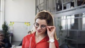 Mujer rubia joven que mira a la c?mara con el grupo de trabajo de hombres de negocios jovenes en el fondo metrajes