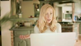 Mujer rubia joven que mira su ordenador portátil chocado repentinamente por lo que ella ve almacen de video