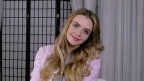 Mujer rubia joven que presenta con el peinado hermoso delante del espejo almacen de metraje de vídeo
