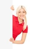 Mujer rubia joven que presenta detrás de un panel en blanco Fotografía de archivo