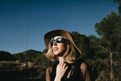 Mujer rubia joven que presenta en naturaleza con las lentes de sol negros y ropa y un sombrero Foto de archivo libre de regalías