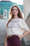Mujer rubia joven que presenta y que sonríe feliz Imagen de archivo libre de regalías