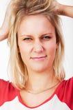 Mujer rubia joven que rasga su pelo Foto de archivo