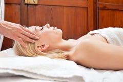 Mujer rubia joven que recibe el masaje principal Imágenes de archivo libres de regalías