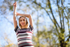 Mujer rubia joven que se coloca en la calle que aumenta sus brazos Imagen de archivo