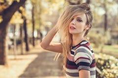 Mujer rubia joven que se coloca en la calle que se mueve el pelo Foto de archivo libre de regalías