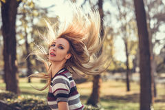 Mujer rubia joven que se coloca en la calle que se mueve el pelo Fotos de archivo libres de regalías