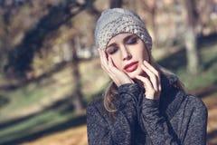 Mujer rubia joven que se coloca en un parque con colores del otoño Imagen de archivo libre de regalías