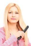 Mujer rubia joven que se endereza el pelo imagenes de archivo