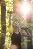 Mujer rubia joven que se resuelve con pesas de gimnasia afuera en foreste fotografía de archivo libre de regalías