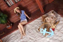 Mujer rubia joven que se sienta cerca de casa de madera en una playa fotografía de archivo