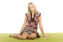 Mujer rubia joven que se sienta en la alfombra verde imágenes de archivo libres de regalías