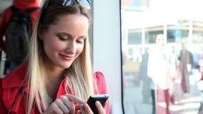 Mujer rubia joven que se sienta en la tranvía, mecanografiando en móvil, teléfono, célula almacen de metraje de vídeo