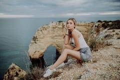 Mujer rubia joven que se sienta en las rocas superiores por el océano Paisaje hermoso de la paz de las playas de Portugal imagenes de archivo