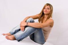 Mujer rubia joven que se sienta en pantalones vaqueros Imagenes de archivo