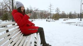 Mujer rubia joven que se sienta en un banco en parque del invierno metrajes