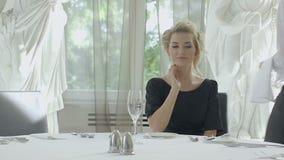 Mujer rubia joven que selecciona el vino en tabla de lujo del restaurante almacen de video