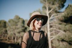 Mujer rubia joven que sonríe en naturaleza con las lentes de sol negros y ropa y un sombrero Fotos de archivo libres de regalías
