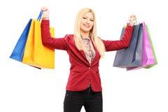 Mujer rubia joven que sostiene bolsos de compras Fotografía de archivo