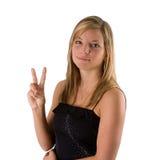 Mujer rubia joven que sostiene dos dedos Imagenes de archivo