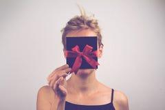 Mujer rubia joven que sostiene una tarjeta con la cinta delante de su fa Imágenes de archivo libres de regalías