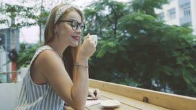 Mujer rubia joven que sueña y que come el café de consumición femenino emocional del resto en la terraza del café almacen de video