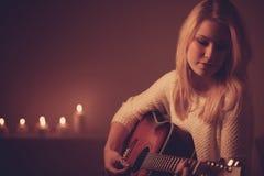 Mujer rubia joven que toca la guitarra en luz de la vela Fotografía de archivo