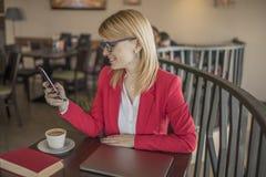Mujer rubia joven que usa el teléfono elegante, mensaje que manda un SMS en la cafetería, restaurante Imagen de archivo
