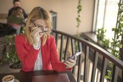 Mujer rubia joven que usa el teléfono elegante, mensaje que manda un SMS en la cafetería, restaurante Imagen de archivo libre de regalías