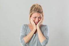 Mujer rubia joven rota corazón que llora expresando sensaciones bajo choque fotografía de archivo libre de regalías