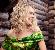 Mujer rubia joven sonriente en alineada verde Foto de archivo