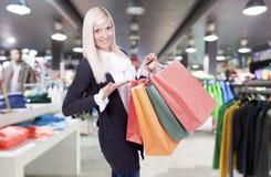 Mujer rubia joven sonriente en tienda de ropa Imagen de archivo libre de regalías