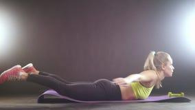 Mujer rubia juguetona en el entrenamiento de la ropa de los deportes para abdominal - levanta para arriba el cuerpo metrajes