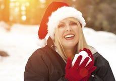 Mujer rubia juguetona en Santa Hat Making Snowballs Outdoors Imagen de archivo libre de regalías