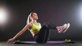 Mujer rubia juguetona que hace el entrenamiento intenso de la aptitud en el gimnasio Atleta de sexo femenino en ropa de deportes almacen de metraje de vídeo