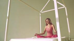 mujer rubia Justo-pelada que hace actitud de la yoga en cama almacen de video