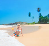 Mujer rubia linda en la playa del océano contra roca y las palmeras Imagen de archivo libre de regalías