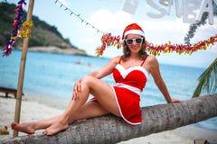 Mujer rubia linda en vestido, gafas de sol rojas y el sombrero de santa que se sienta en la palmera en la playa tropical exótica  Imagenes de archivo